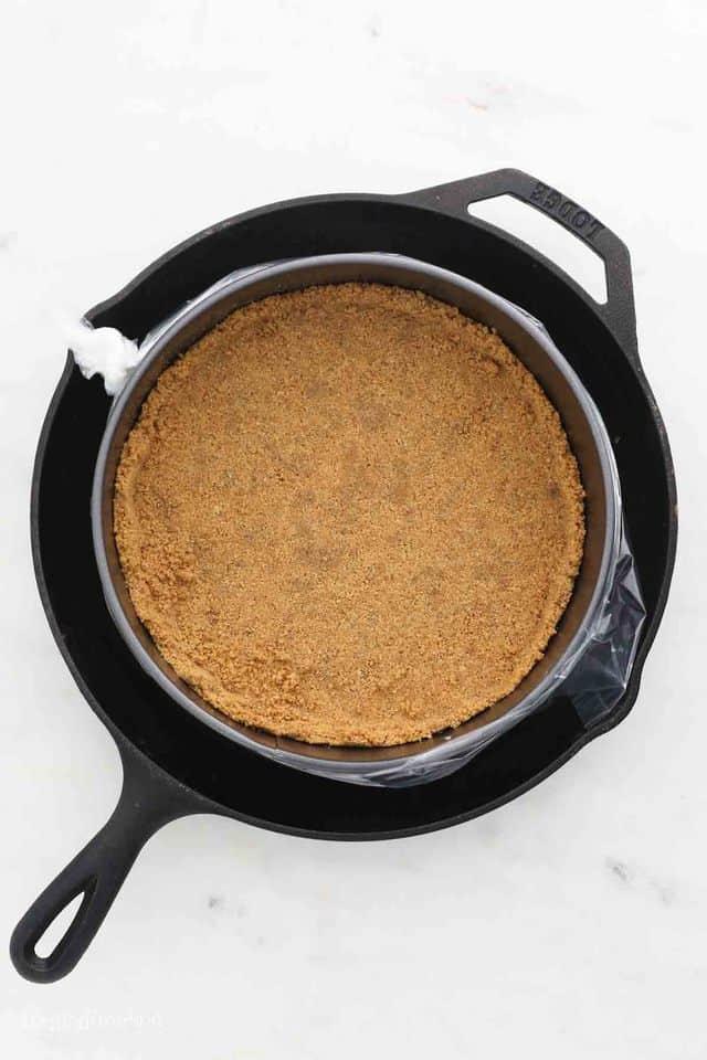 Graham cracker crust in a springform pan, inside a large cast iron pan.
