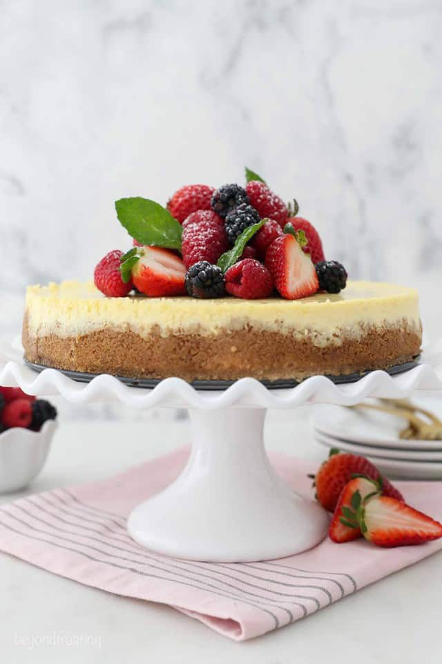 A creamy homemade cheesecake with graham cracker crust, topped with fresh strawberries and blackberries
