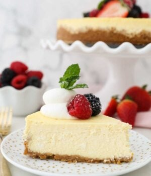 A slice of cheesecake topped with whipped cream and berries. In the back is the full cheesecake.
