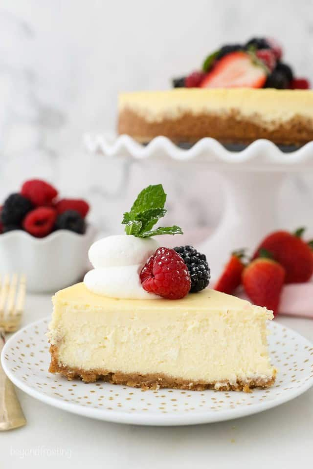 A slice of creamy homemade cheesecake topped with whipped cream and berries. In the back is the full cheesecake.