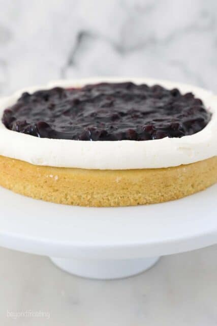 a layer of cake with a boarder of frosting and blueberry pie filling in the middle