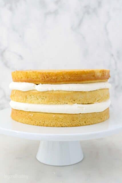 a white cake stand with 3 layers of cake stacked