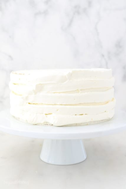a white cake stand with a layer cake roughly frosted