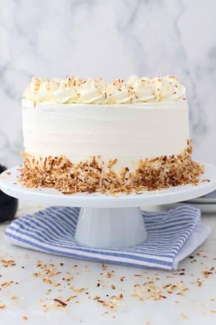 a white cake plate on a blue napkin. A frosted cake with toasted coconut