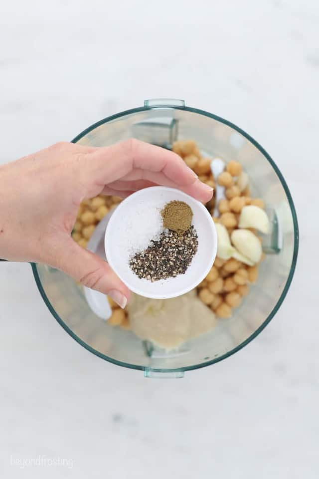 A Bowl of Spices Above a Food Processor Holding the Other Hummus Ingredients