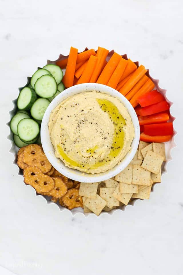 An Appetizer Tray with Homemade Hummus, Carrots, Pretzels, Crackers and Cucumbers