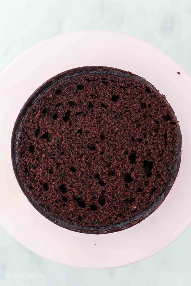 Bird's eye view of a layer of chocolate cake, flattened on top, sitting on a pink cake stand