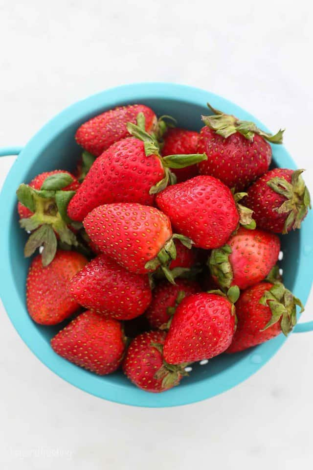A Teal Bowl Containing Fresh Strawberries on a Countertop