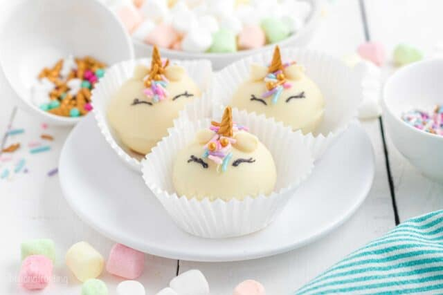Three Unicorn hot chocolate bombs in cupcake wrappers sitting on a white plate