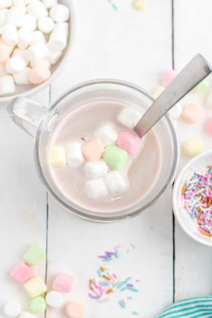 Bird's eye view of a spoon in a glass with hot chocolate and colorful marshmallows