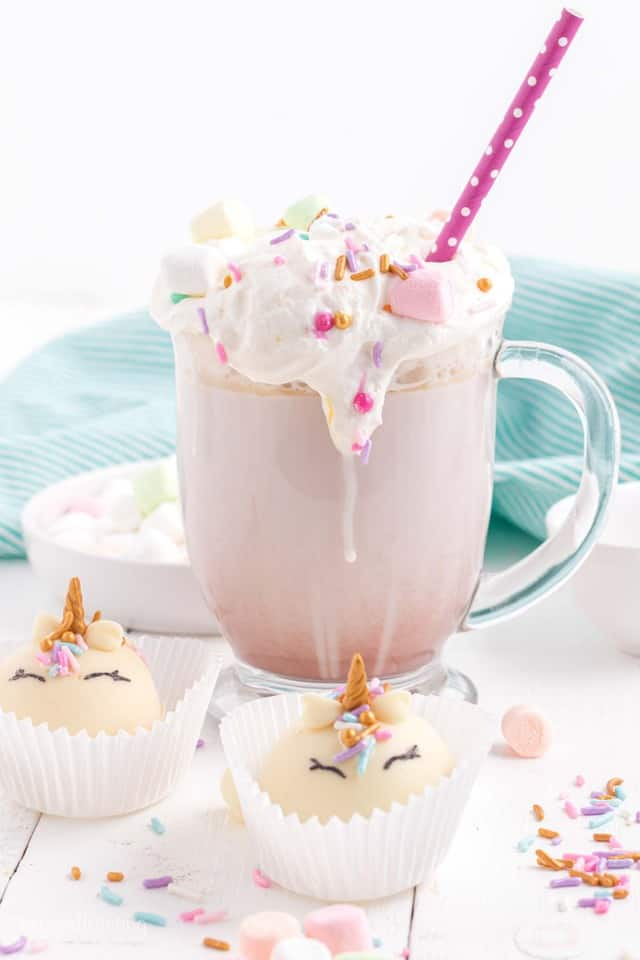 Glass mug with hot chocolate, whipped cream and colorful sprinkles with marshmallows