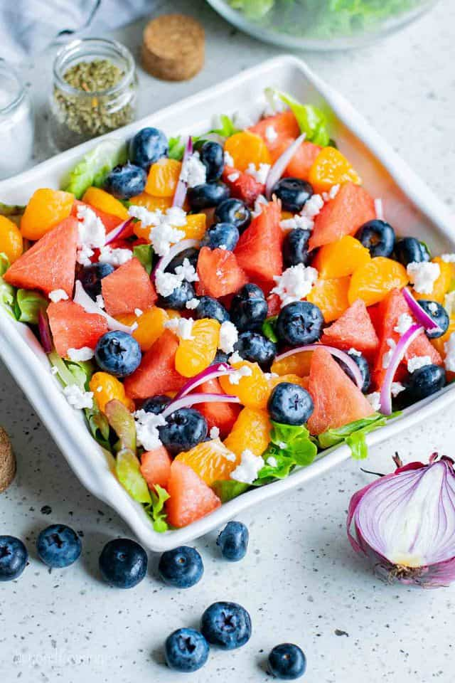 A Square Plate of Salad on a Speckled Countertop with Scattered Blueberries