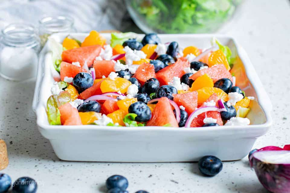 A Serving Platter on a Countertop Filled with Watermelon Mandarin Feta Salad