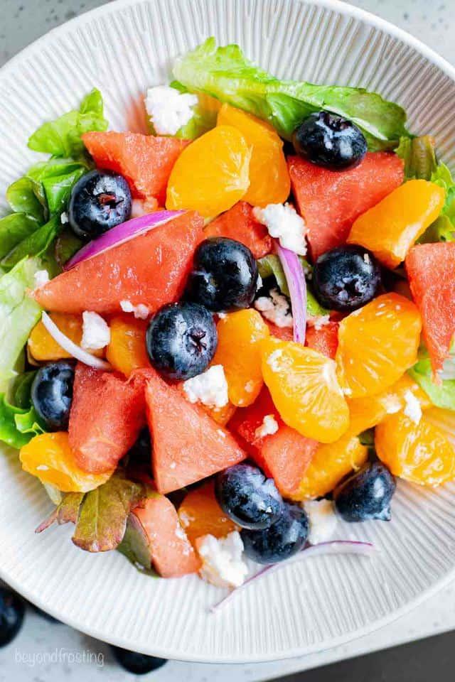 A Watermelon Mandarin Feta Salad on a White Plate with a Textured Rim