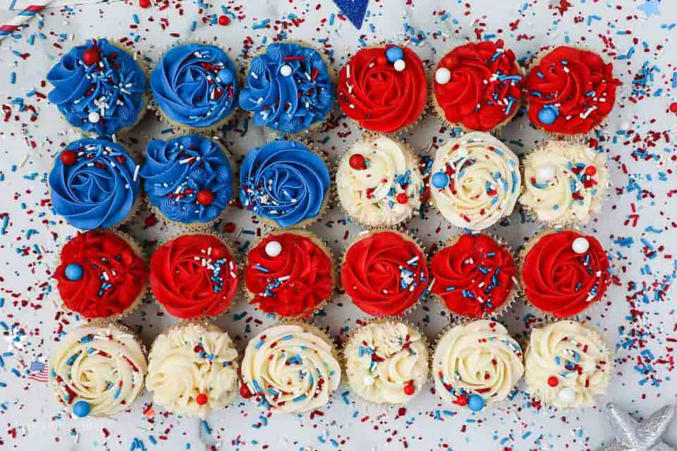 Birds eye view 24 cupcakes frosted in red white and blue laid out like a flag with lots of sprinkles
