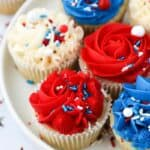 close up of red, white and blue frosted cupcakes on a white plate