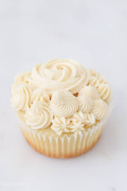 a frosted vanilla cupcake on a marble background