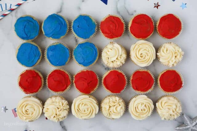 Birds eye view 24 cupcakes laid out like a flag, the white ones are frosted