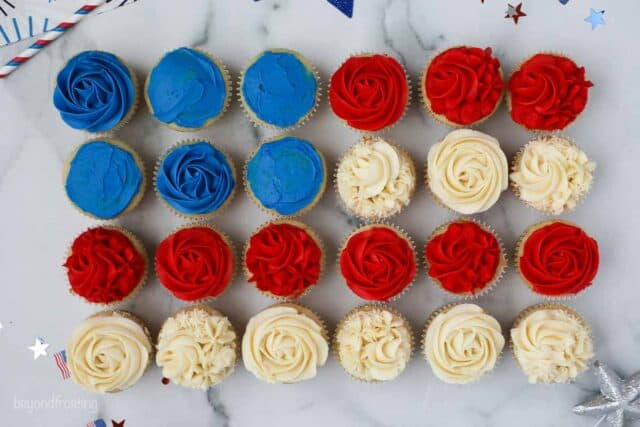 Birds eye view 24 cupcakes frosted in red white and blue laid out like a flag