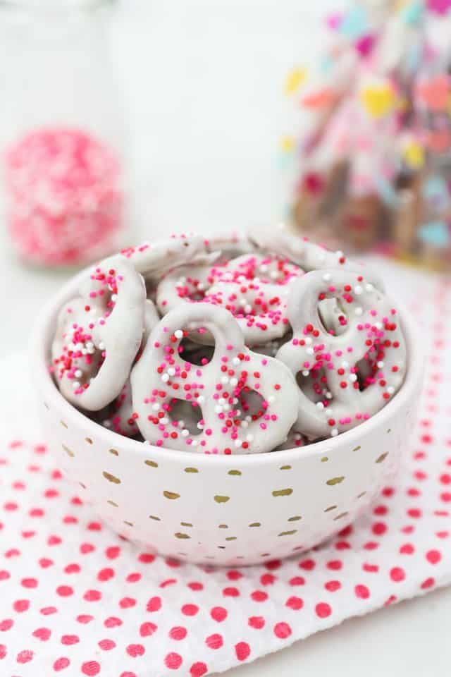 A bowl of white chocolate covered pretzel twists with pink sprinkles in a bowl