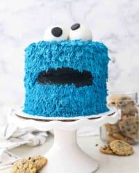 a white cake stand with a cookie monster cake and a jar of cookies in the background