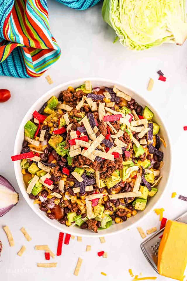 Aerial view of a big bowl of taco salad with ground beef, topped with cheese and tortilla strips