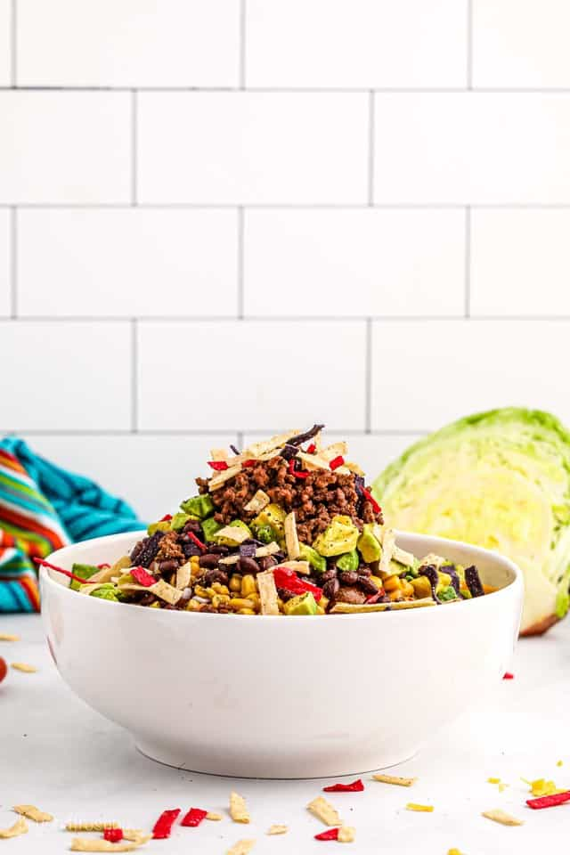 A big bowl of taco salad piled with veggies, tortillas, avocado and ground beef