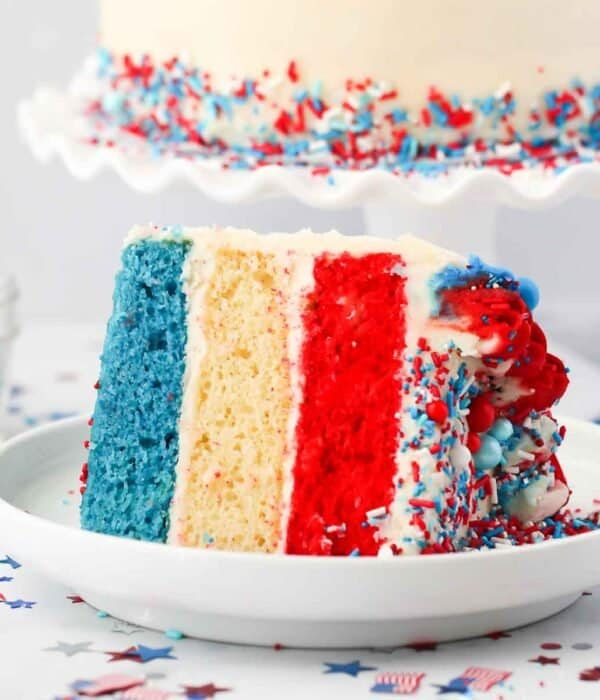 a slice of 3 layer cake with layers of blue, white and red cake. Patriotic confetti on the table.