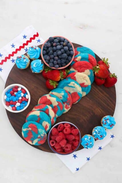 a round wooden board with three dishes filled with fruit, cookies in the middle and cupcakes on the side