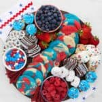 a round wooden board filled with red, white and blue themed desserts like cookies, candies and donuts