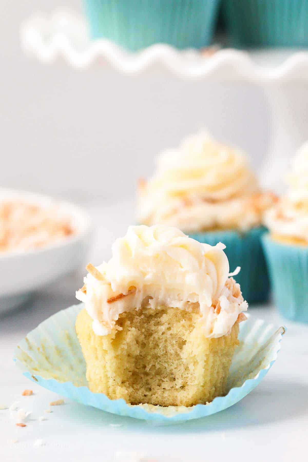 A coconut cupcake with frosting in a cupcake wrapper, with a bite missing.