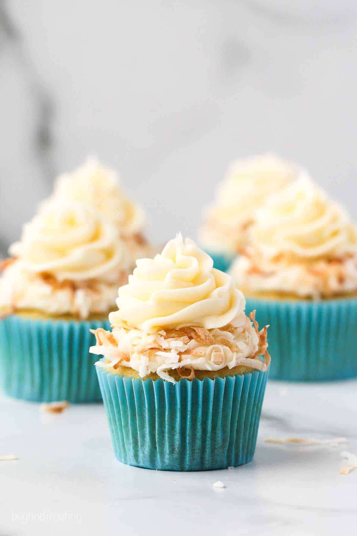 Three coconut cupcakes piled high with frosting