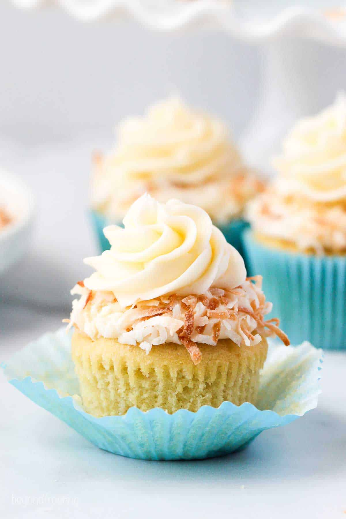 A coconut cupcake topped with cream cheese frosting and toasted coconut