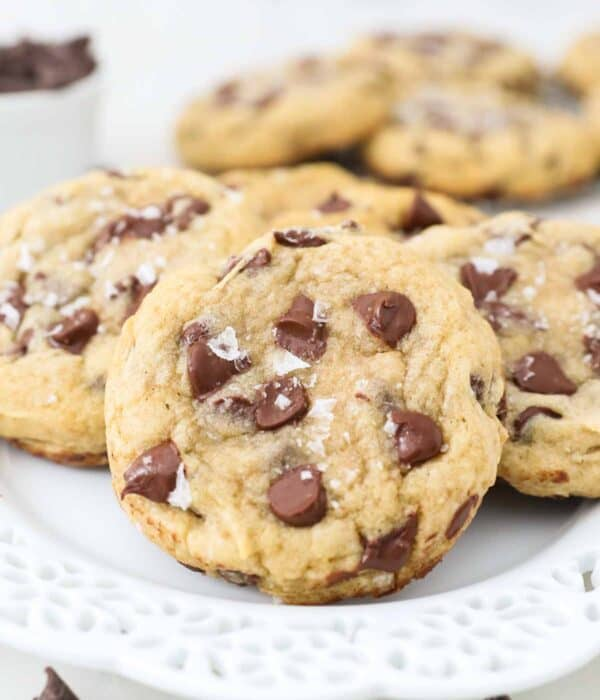 Gluten-free chocolate chip cookies topped with sea salt on a white plate