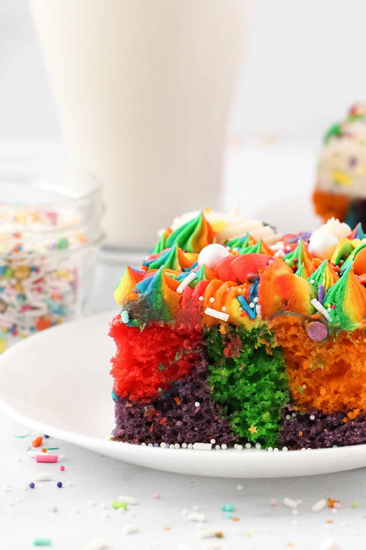 A slice of rainbow cake with a glass of milk in the background