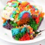 A slice of rainbow cake with one piece on a fork