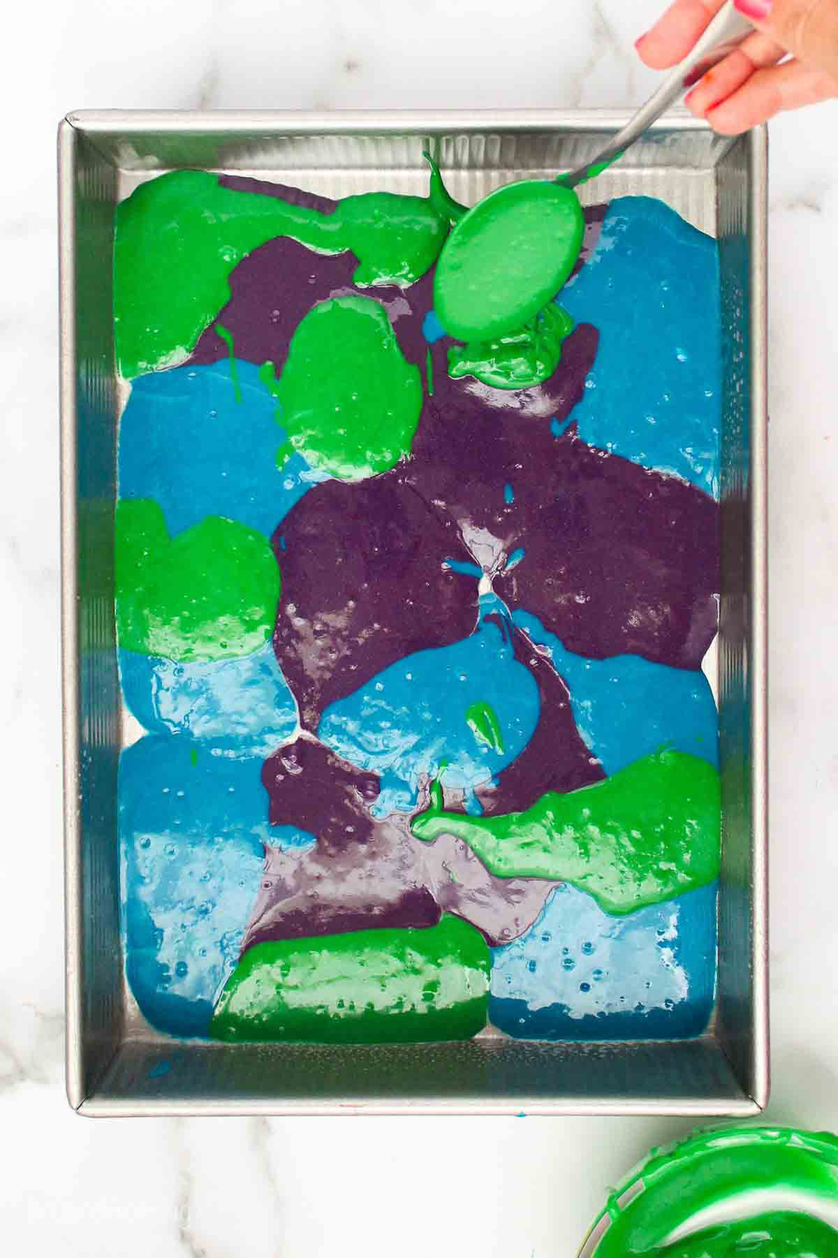 Spoonfuls of purple, blue and green cake batter in a pan