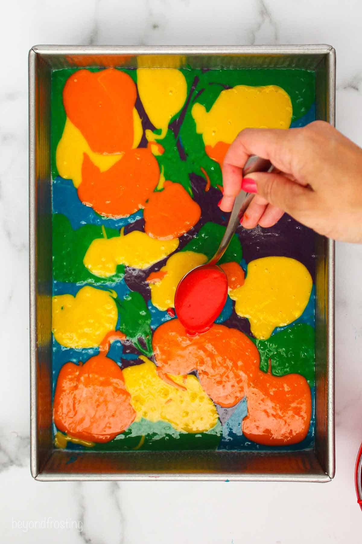 Spoonsfuls of blue, purple, green, yellow and orange cake batter layers in a pan