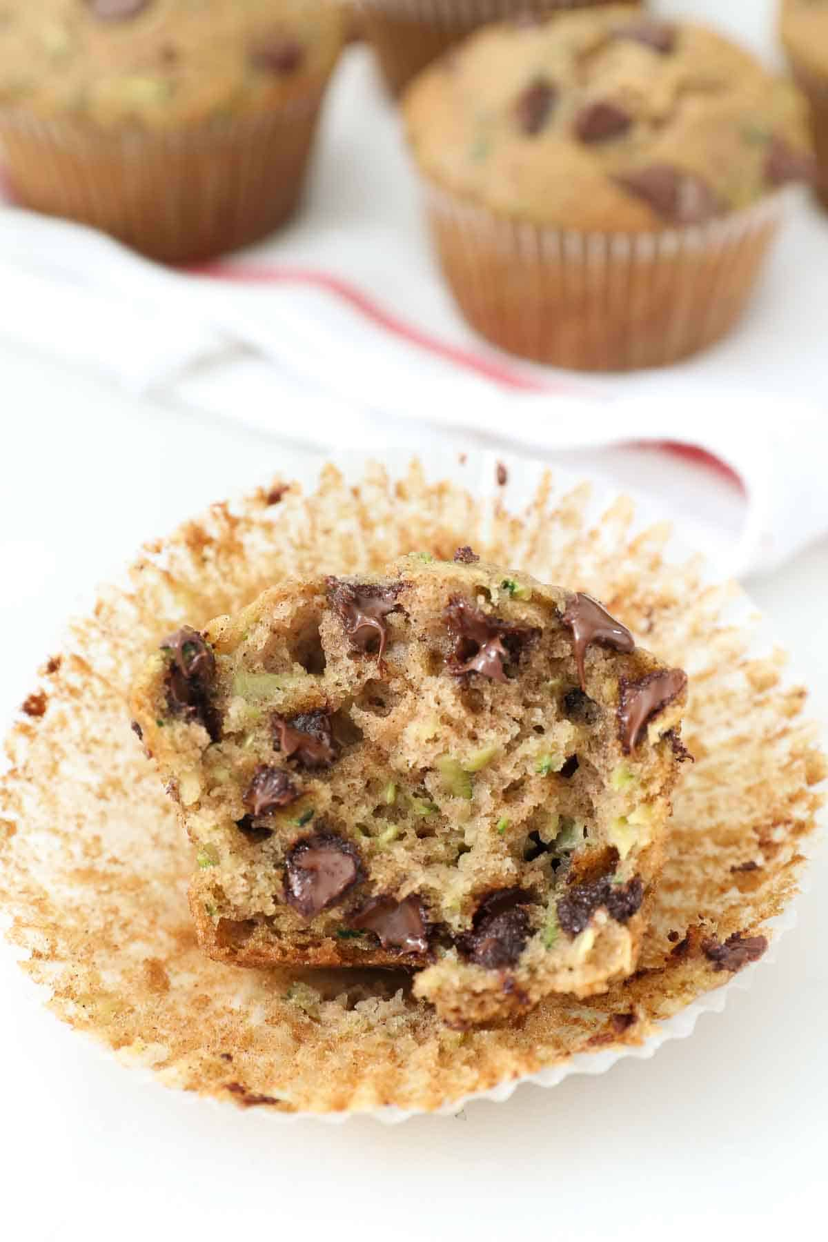 A half-eaten zucchini muffin with chocolate chips