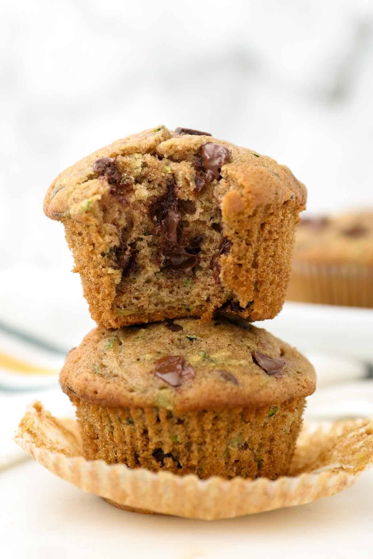 Two chocolate chip zucchini muffins stacked on each other, the top one with a missing bite