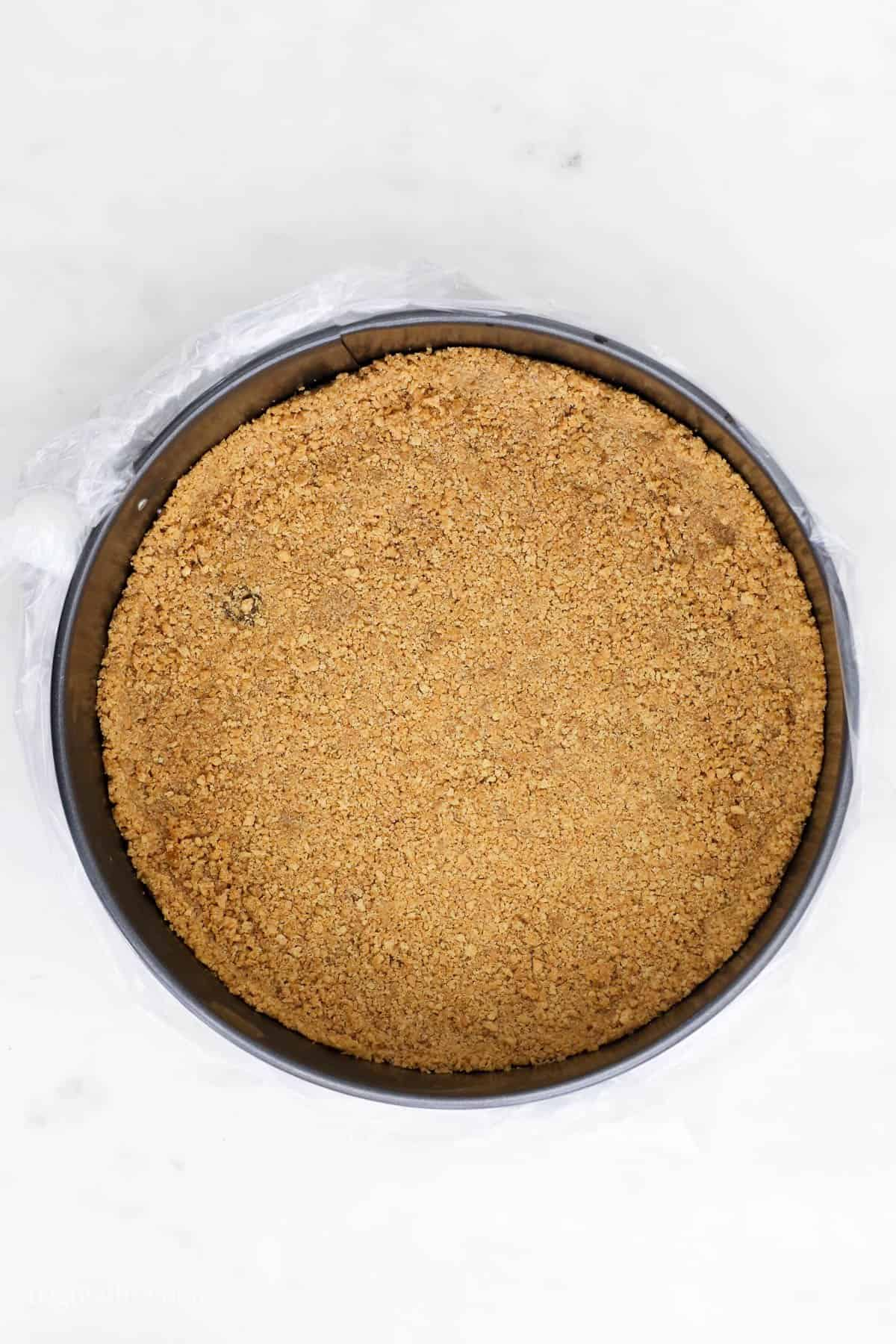 overhead view of a graham cracker crust in a springform pan