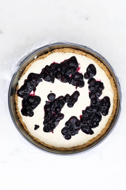 overhead view of a cheesecake batter in a pan with drops of blueberry sauce
