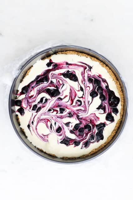 overhead view of an unbaked cheesecake swirled with blueberry sauce