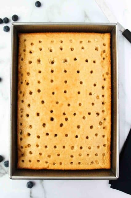 overhead shot of a cake with holes poked in it