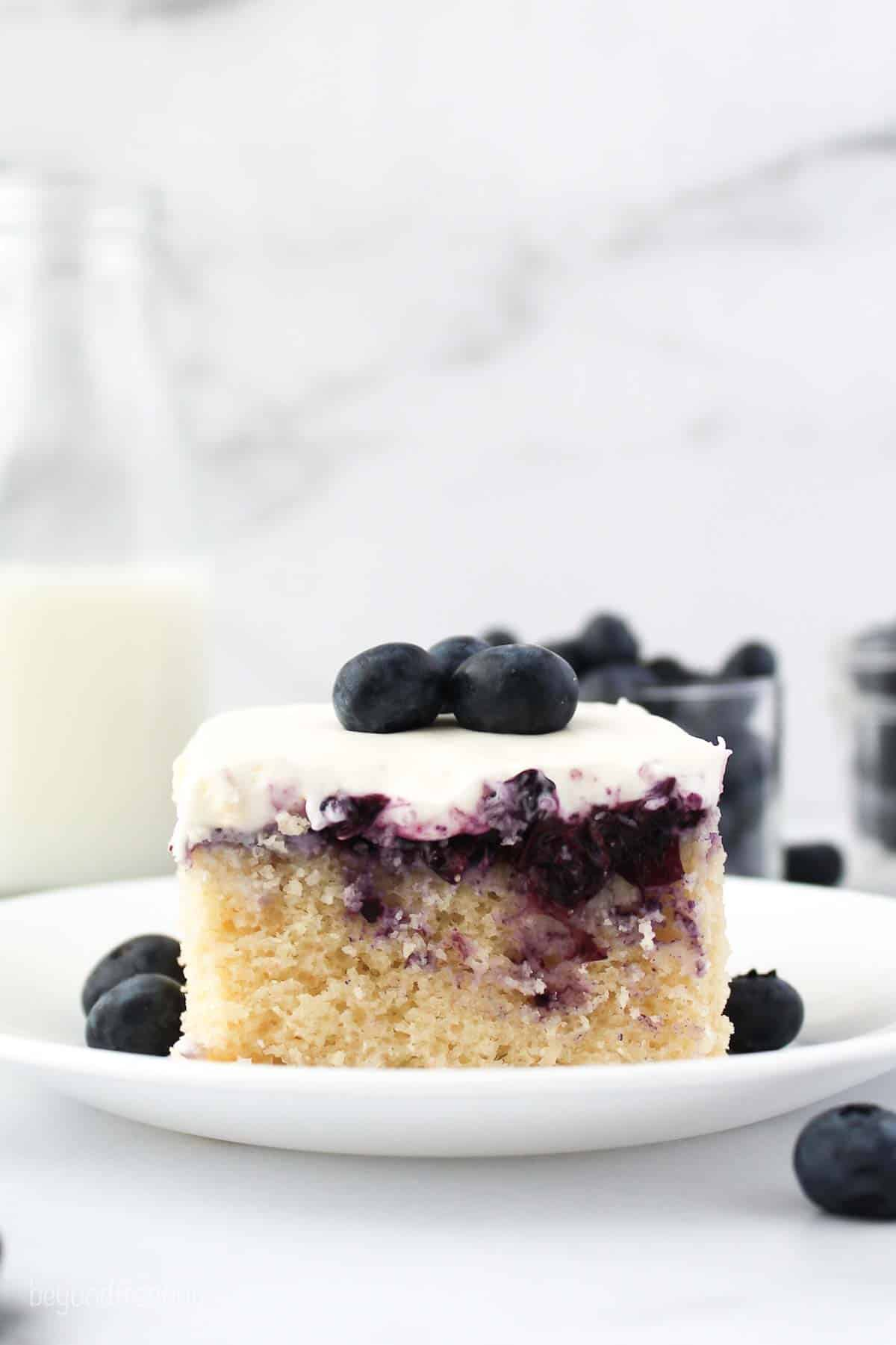 A slice of cake with blueberry filling on a white plate