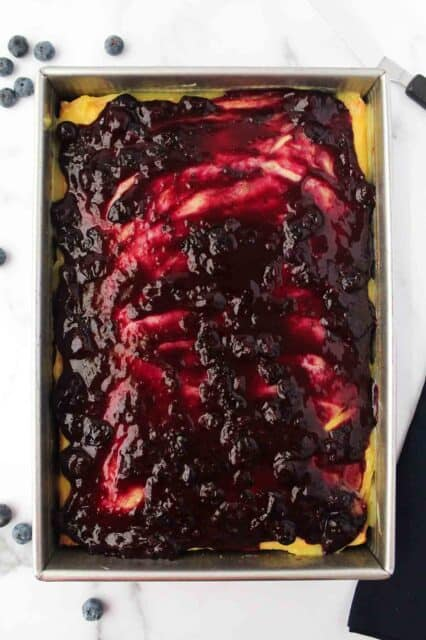 blueberry sauce spread overtop of a cake