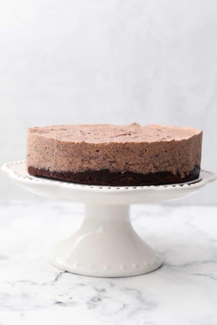 a white cake stand with a two layer chocolate cake