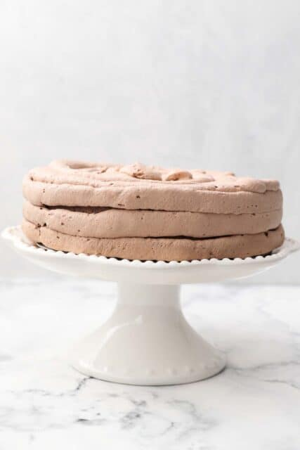 a white cake stand with a cake being frosted with chocolate whipped cream