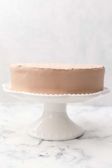 a white cake stand with a small layer cake frosted with chocolate whipped cream
