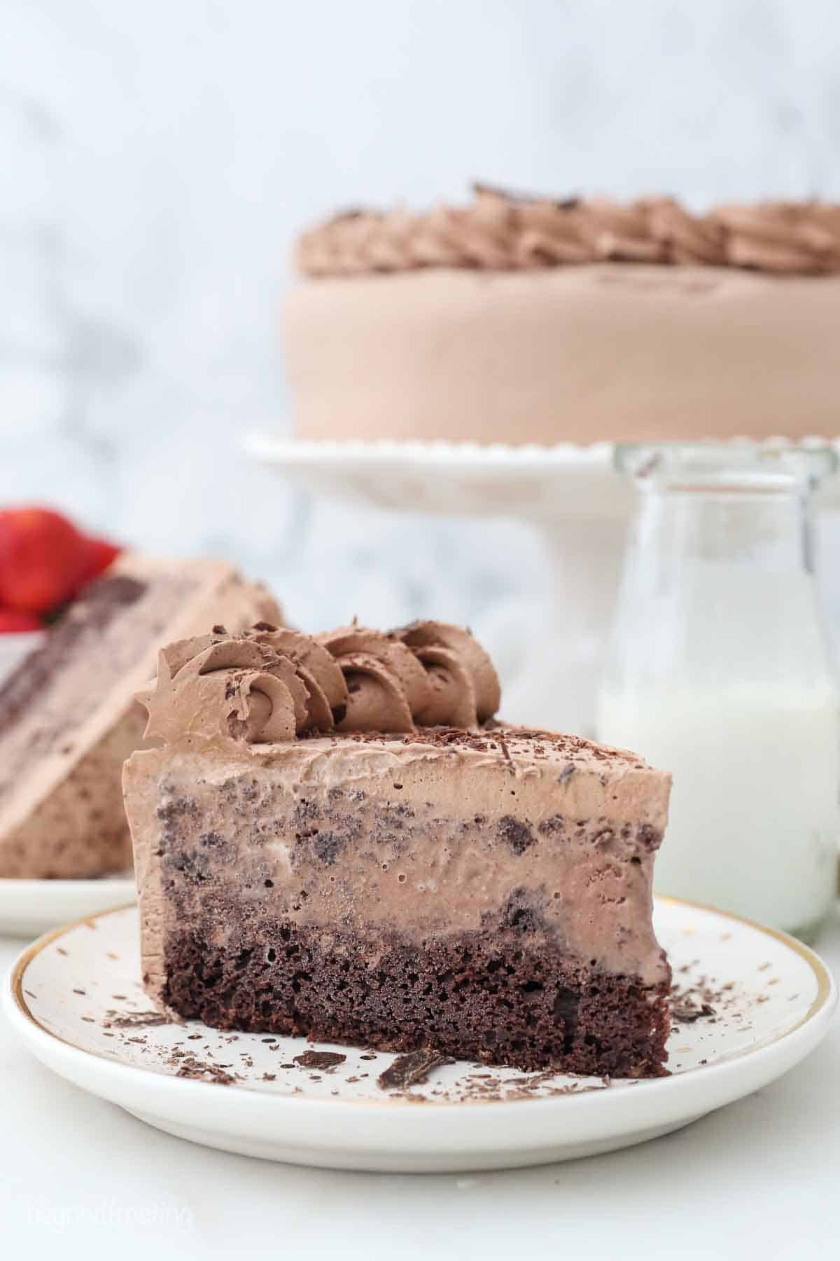 a slice of two layer chocolate ice cream cake on a plate with a glass of milk